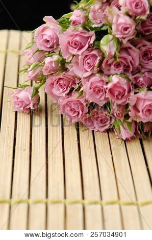 pink branch rose on wooden mat background