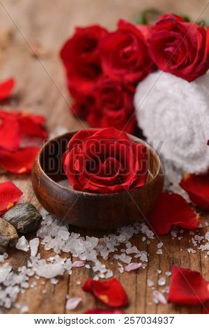 Red rose in bowl with pile of salt ,stones with rolled towel on old wooden