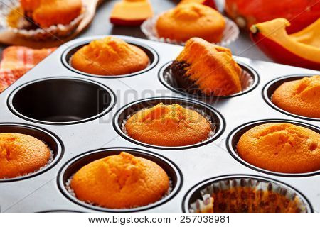 Close-up Of Freshly Baked Homemade Sweet Pumpkin Muffins In A Baking Mold On A Rustic Wooden Table,
