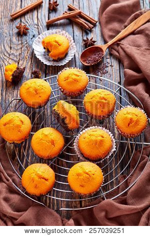 Freshly Baked Delicious Sweet Pumpkin Muffins  On A Round Stainless Steel Cake Cooling Rack On A Rus