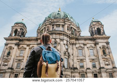 A Tourist Or Traveler With A Backpack Looks At A Tourist Attraction In Berlin Called Berliner Dom. T