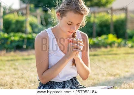 Christian Worship And Praise. A Young Woman Is Reading The Bible In The Early Morning.