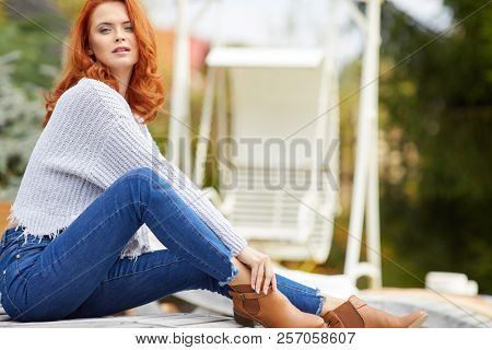woman is sitting on the terrace in front of the house. Autumn scene