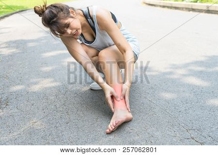 Woman Painful Legs, Ankle Muscle Pain. Young Asian Girl Hurt From An Ankle Injury. Runner Female Mas