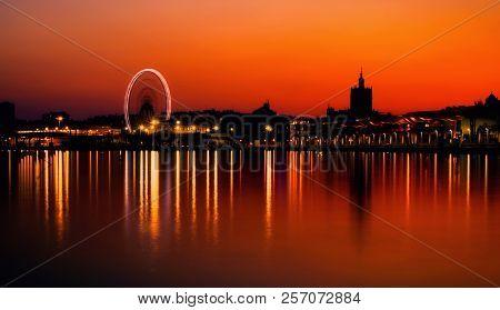 Sunset Over Ferris Wheel And Malaga Port Promenade Muelle Uno At Malaga City, Costa Del Sol, Andaluc