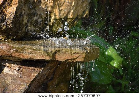 Garden Waterfall Of Stones. Water Flows Through The Stone. The Morning Sun Shines On The Waterfall
