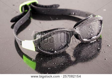 Swimming Goggles Over Reflecting Black Background, Horizontal Image