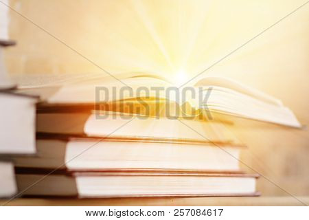 Pile Of Books With Open Book With Rays Of Light. The Concept Of Knowledge And Enlightenment. Bookshe