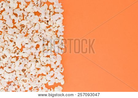 Popcorn Scattered At Half The Orange Background Background And A Space For Copyspace. Popcorn On A R