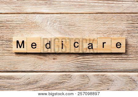 Medicare Word Written On Wood Block. Medicare Text On Table, Concept.