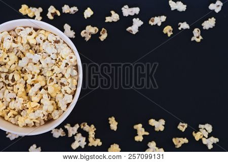 Paper Cup With Popcorn, And Popcorn Scattered On A Black Background, Top View, Copyspace. Flat Lay.