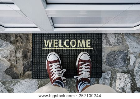 Welcome. Entering House. Man Legs In Sneakers Standing On Stairs Next To Line And Word Welcome And P
