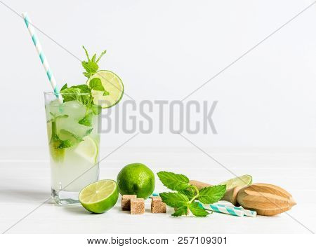 Non-alcoholic cocktail mojito with ingredients for its preparation on a white background
