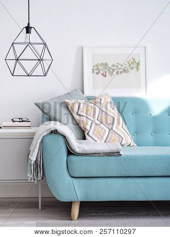Vibrant Sofa Decorated With Cushions And Woolen Plaid, Small Cabinet Under Stylish Lamp In Bright Su