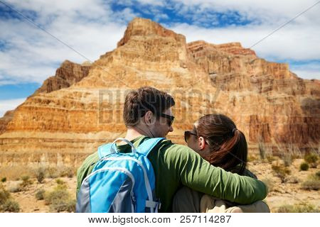 travel, hiking, backpacking, tourism and people concept - happy couple of travelers with backpacks hugging over grand canyon national park background
