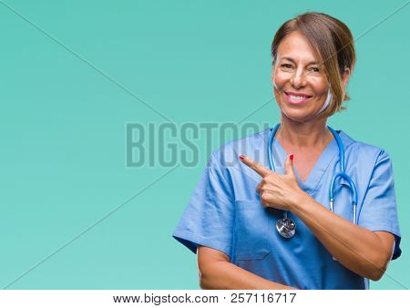 Middle age senior nurse doctor woman over isolated background cheerful with a smile of face pointing with hand and finger up to the side with happy and natural expression on face