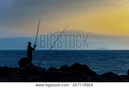 Silhouette Of A Fisherman At Sunrise In The Sea