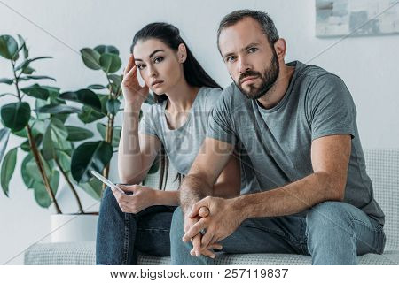 Sad Stressed Couple With Pregnancy Test Sitting And Looking At Camera