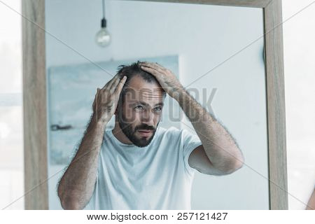 middle aged man with alopecia looking at mirror, hair loss concept poster
