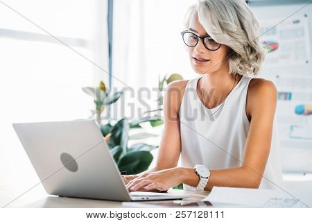 Beautiful Caucasian Businesswoman Using Laptop In Office
