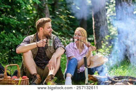 Couple Take Break To Eat Nature Background. Couple In Love Camping Forest Hike. Couple Sit Near Bonf