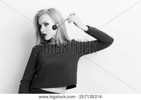 Model With Powder Brush Applying Makeup On Face Skin. Pretty Woman With Blond Long Hair Wearing Blue