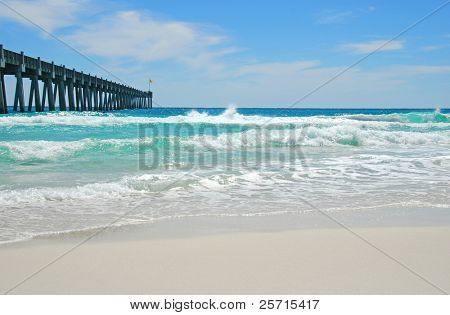 Fishing Pier at Deserted Beach with Crashing Waves in Distance