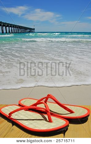 Straw Flip Flops on Dock Next to Ocean Pier