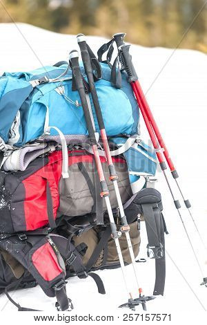 Three Backpacks On The Background Of Snow-capped Mountains And Blue Sky. A Backpack On The Snow. Act
