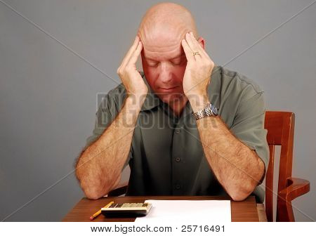 Middle Aged Man Looking Stressed Over Calculator