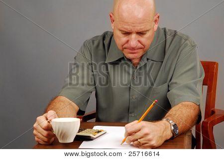 Hombre a beber café, trabajando en el presupuesto con la calculadora de escritorio