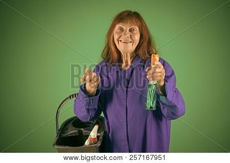 Woman with long hair hold soup bottle. Cleaning and purity. Old lady cleaner with bucket on green background. Housekeeper woman in uniform with clean spray. Cleanup and order services. poster