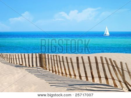 Pretty Beach and fence with ocean and sailboat in distance