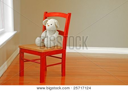 Stuffed bear in red wooden chair looking out window