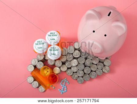 Flat Lay Of Pink Piggy Bank Next To Stacks Of Coin Cash Piled High Around Rx Prescription Drugs, Pil