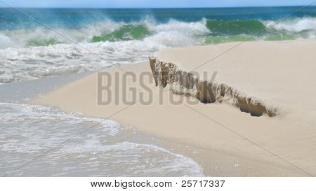 Crashing surf on beautiful beach with mild erosion of sand dune