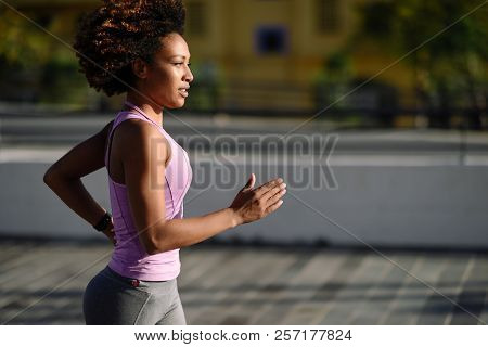 Black Woman, Afro Hairstyle, Running Outdoors In Urban Road. Young Female Exercising In Sport Clothe