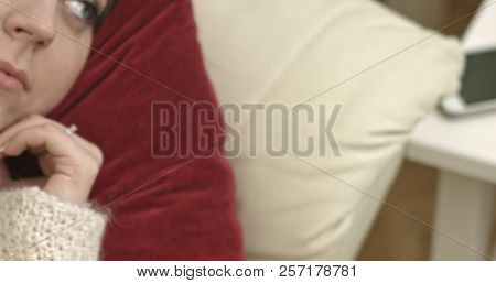 Serene young woman lying on sofa with open eyes. It's her relax time. The camera move from her.