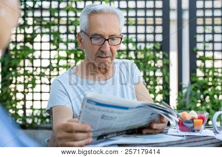 Elderly man with eyeglasses reading an article in the newspaper. Senior man with serious expression reading news while sitting at breakfast table. Mature man reads bad news on paper.