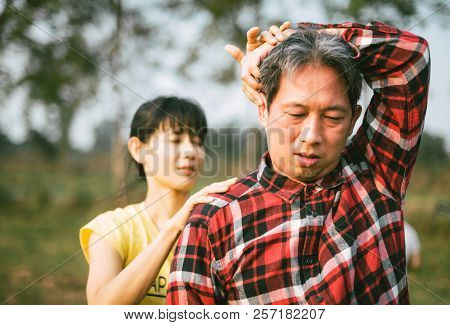 Asian women physical therapist Chiropractic back adjustment. Muscular Man suffering from back and neck pain to the male patient. poster