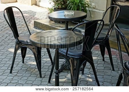 Black Wooden Tables And Chairs On The Sidewalk In The Street