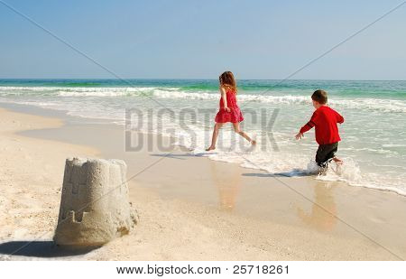 Younger brother chasing sister through water at beach with sand castle in foreground