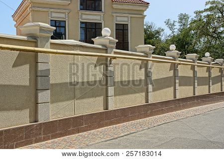 Brown Concrete Fence In Front Of A House In The Street Near An Asphalt Road