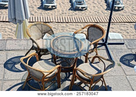 Brown Table And Chairs On The Open Terrace By The Beach With Sand And Sun Beds