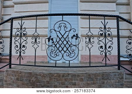 Threshold With A Decorative Iron Fence With Rods With A Forged Pattern Near The Wall