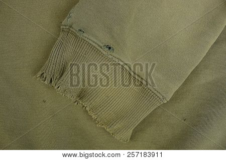 Green Fabric Texture With A Sleeve Of A Piece Of Ragged Old Clothes
