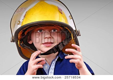 Cute young toddler boy wearing real fireman's helmet