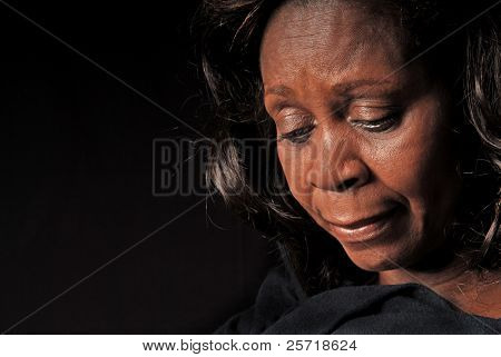 Serious or somber beautiful black woman looking down