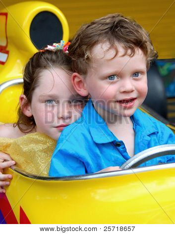 Young brother and sister sitting together in race car