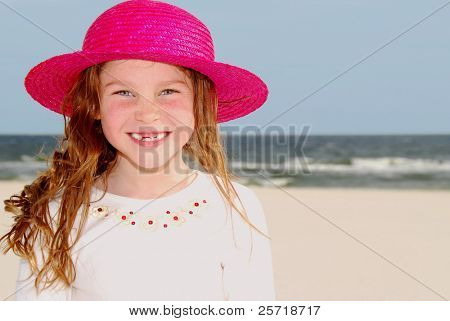 Happy girl wearing pink straw hat on beach